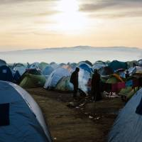 People stand among tents pitched in a makeshift camp at the Greek-Macedonian border near the Greek village of Idomeni on Sunday. | AFP-JIJI