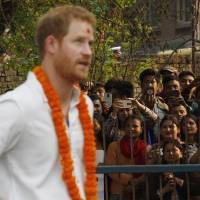 People take photos as Britain's Prince Harry visits a pre-positioning site, containing earthquake relief supplies, in Bhaktapur, Nepal, Sunday. | AP