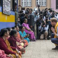 Britain's Prince Harry interacts with a group of local women while he visits the Golden temple in Patan Durbar in Patan, Nepal, Sunday. Patan Square, a UNESCO World Heritage Site, was damaged during the 2015 earthquake. The Prince is on a five-day trip to Nepal. | REUTERS