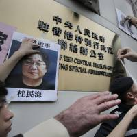 Protesters post images of missing booksellers at the Beijing liaison office in Hong Kong. At left is a picture of detained storekeeper Gui Minhai. | AP