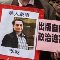 A protestor holds up a missing person notice for Lee Bo, 65, in this photo taken in Hong Kong on Jan. 3. Hong Kong police said Thursday that Lee had returned to Hong Kong. | AFP-JIJI