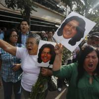 Activists hold photos of slain environmental rights activist Berta Caceres and shout after her body was released from the morgue in Tegucigalpa Thursday. | REUTERS