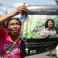 A woman holds up a poster with a photo of slain environmental leader Berta Caceres during a protest march in Tegucigalpa Wednesday. Authorities said that unidentified gunmen killed Nelson Garcia, a colleague of Caceres, who was slain almost two weeks ago in similar circumstances. | AP