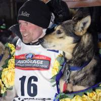 Dallas Seavey poses with his lead dogs Reef (left) and Tide after finishing the Iditarod Trail Sled Dog Race March 15 in Nome, Alaska. Seavey won his third straight Iditarod, for his fourth overall title in the last five years. | AP