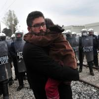 A migrant carrying his child stands in front of riot police during a protest of migrants Sunday at the Greek-Macedonian border, near the Greek village of Idomeni, where thousands of refugees and migrants are stranded by the Balkan border blockade. Dozens of hopeful refugees, some carrying babies, rushed to Greece's overwhelmed Idomeni camp on the sealed border with Macedonia following rumors that the frontier would be forced open. | AFP-JIJI