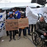A migrant in a wheelchair and boys holding placards reading 'Don't beat us' and 'help us' stand in front of riot police during a protest of migrants at the Greek-Macedonian border, near the Greek village of Idomeni on Sunday. | AFP-JIJI