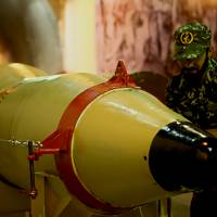A member of the Revolutionary Guards stands next to a missile launcher in an underground tunnel at an undisclosed location in Iran. | SEPAH NEWS / AFP-JIJI