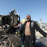 A man reacts at the site of a bomb attack at a checkpoint in the city of Hilla, south of Baghdad, Sunday. | REUTERS