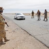 Libyan soldiers manning a military outpost, stop a car at a checkpoint in Wadi Bey, west of the city of Sirte, which is held by Islamic State militants, last month. | REUTERS