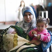 Syrian refugee Kholod, who got married 30 months ago in the camp, carries her daughters Fedaa' (right) and Rima during a ceremony held by UNFPA maternal clinic marking the birth of 5,000 babies with no maternal deaths, at Al Zaatari refugee camp in the Jordanian city of Mafraq, near the border with Syria, Tuesday Rima is the 5,000th baby to be born safely in Zaatari camp clinics. | REUTERS