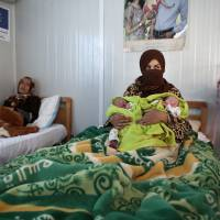 Syrian refugee Maan Turkman, 31, holds her twin infants Mohammed (left) and Ahmed in July at a maternity clinic in Zaatari refugee camp, in Mafraq, Jordan. The U.N. Population Fund says its clinic in Jordan's largest camp for Syrian refugees has safely delivered more than 5,000 babies since opening in 2013. | AP