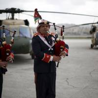 Members of a Jordanian police band perform during a handover ceremony held to deliver Black Hawk helicopters to Jordan from the U.S. government at Amman military airport Thursday. | REUTERS