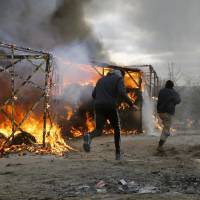 Migrants run past burning tents in a makeshift camp near Calais, France, Monday. French authorities have begun dismantling part of the sprawling camp locally referred to as 'the Jungle' where thousands are hanging out, hoping to make their way to a better life in Britain. | AP