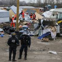 Razing continues of France's rain-soaked 'Jungle' refugee camp