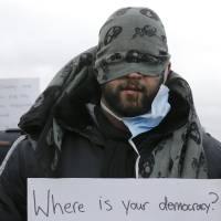 An Iranian migrant, with his lips sewn, holds a message, 'Where is your democracy' in protest of the partial dismantlement of the shanty town called the 'Jungle' in Calais, France, Wednesday. | REUTERS