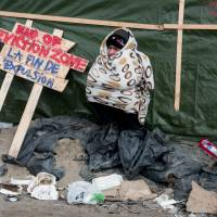 A man sits next to a placard in the northern part of the 'Jungle' migrant camp in Calais, northern France, during the end of the dismatling of the camp's southern part, on Wednesday. France's first international-standard refugee camp opened in northern France on March 7 destined to shelter migrants and refugees living in dire conditions in nearby makeshift camps as they attempt to reach the United Kingdom. | AFP-JIJI