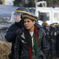 A French CRS riot policeman apprehends a young Afghan during a protest by migrants against the partial dismantlement of the camp for migrants called the 'Jungle' on Monday. | REUTERS