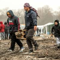 Migrants carry pieces of wood they collected during the dismantling of half of the 'Jungle' migrant camp in the French northern port city of Calais on Tuesday. | AFP-JIJI