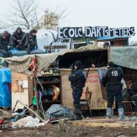 French riot police keep watch during the end of the dismantling of the southern part of the 'Jungle' migrant camp in Calais, northern France, Wednesday. | AFP-JIJI
