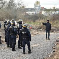 A migrant faces anti-riot policemen on Monday during the dismantling of half of the 'Jungle' migrant camp in the French northern port city of Calais. | AFP-JIJI