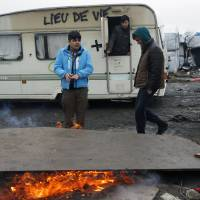 Migrants burn wood to keep warm, with a railer bearing a sign reading 'living space' in a makeshift migrant camp near Calais, France, Tuesday. | AP
