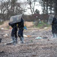 French riot police protect themselves from a hailstorm, during the demolition of the southern part of the 'Jungle' migrant camp, on Wednesday. | AFP-JIJI
