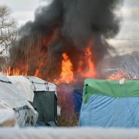 A shack is burning during the dismantling of half of the 'Jungle' migrant camp in the French northern port city of Calais Monday. | AFP-JIJI