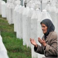 Bida Smajlovic, 64, a survivor of July 1995 massacre in Srebrenica, prays by her husband's grave at a memorial center in Potocari, on Thursday. | AFP-JIJI