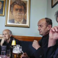Men follow on online media the verdict in the trial of former Bosnian Serb leader Radovan Karadzic, in a local bar on the outskirts of Belgrade on Thursday. | NEMANJA PANCIC / AFP-JIJI