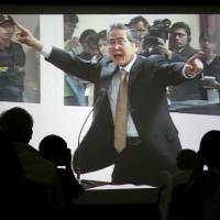 Live video of former Peruvian President Alberto Fujimori is shown on Dec. 10, 2007, the first day of his trial in connection with human rights violations and corruption, at the press center of the Lima police base where the trial took place. | AP