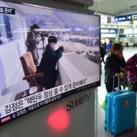 Travelers walk past a public television screen showing file footage of North Korean leader Kim Jong Un, at a railway station in Seoul on Friday. Kim has ordered its nuclear arsenal readied for pre-emptive use at anytime, in an expected ramping up of rhetoric following the U.N. Security Council's adoption of tough new sanctions on Pyongyang. | AFP-JIJI