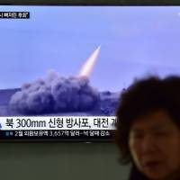 A woman walks past a public television screen showing file footage of a North Korean missile, at a railway station in Seoul on Friday. | AFP-JIJI