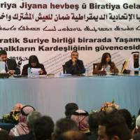 Aldar Khalil (center),from the Democratic Union Party (PYD), and Sheikh Hamad Sheikh Shihadeh (right), the Naim clan chief in northern Syria, speak during a meeting of more than 150 delegates from Kurdish, Arab, Assyrian and other parties in the town of Rmeilan, in Syria's northeastern Hassakeh province, on Wednesday. Kurdish-led parties meeting in northern Syria are expected to declare a new federal system in areas under their control, Kurdish officials told AFP on Wednesday. The move, which would expand an already existing system of self-administration, is likely to anger Turkey, which is wary of any bid by Syrian Kurds to solidify their autonomy and their control of territory. | AFP-JIJI