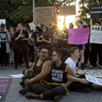 Demonstrators (front, from left) Jess Jude, Loan Tran and Noah Rubin-Blose sit chained together in the middle of the street during a protest over House Bill 2 March 24 outside of the Governor's Mansion on North Blount Street in downtown Raleigh, North Carolina.   JILL KNIGHT / THE NEWS