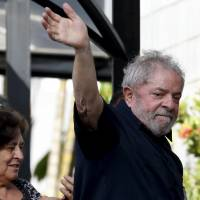 Luiz Inacio Lula da Silva waves to supporters as he arrives at his apartment building in Sao Paulo on Friday after being detained for questioning in a federal investigation of a bribery and money laundering scheme. | REUTERS