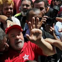 Former Brazilian President Luiz Inacio Lula da Silva is greeted by supporters in front of his home in Sao Bernardo do Camopo on Saturday, a day after he was questioned by police investigating a huge corruption scandal. | REUTERS
