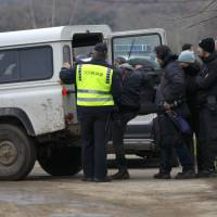 Macedonian police escort journalists who have crossed the border illegally from Greece, into a vehicle in the village of Moini, Macedonia, Monday. | REUTERS