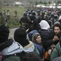 Macedonian border police round up migrants after they illegally crossed the Greek-Macedonian border in the village of Moin near the southern Macedonian town of Gevgelija on Monday. Hundreds of migrants and refugees walked out of an overcrowded camp on the Greek-Macedonian border Monday, determined to use a dangerous crossing to head north. | AP