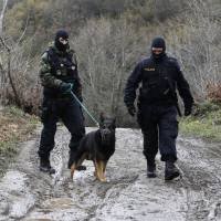 Czech Republic police with a dog patrol along a muddy road on the border line with Greece at the village of Moin, near the southern Macedonia town of Gevgelija, Tuesday. Hundreds of migrants walked out Monday of an overcrowded camp on the Greek-Macedonian border in an effort to circumnavigate border controls and travel north toward Central Europe, but were returned to Greece. | AP