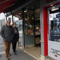 Residents watch the first meat vending machine installed in Paris on Tuesday. With their beloved baguette already available 24 hours a day, it seems only logical that Parisians can now get the Bayonne ham and Basque pate that goes so well with it from the first meat vending machine in the capital. | AP