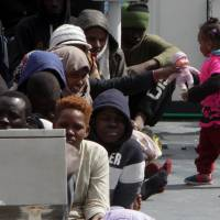 A girl plays with a doll as migrants and refugees wait to disembark in the port of Messina following a rescue operation at sea by the Italian Coast Guard ship Diciotti on Thursday in Sicily. More than 2,400 migrants and three corpses have been recovered from people smugglers' boats off Libya Italy's coast guard said. After several quiet weeks, the figures represent a pick-up in the flow of migrants attempting to reach Italy via Libya. | AFP-JIJI