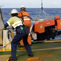 Workers aboard search ship Fugro Discovery recover a deepwater sonar unit in this undated file photo. | ABIS CHRIS BEERENS