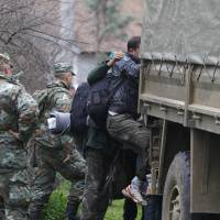 Macedonian soldiers escort migrants who have crossed the border illegally from Greece, into army trucks in the village of Moini, Macedonia, Monday. | REUTERS