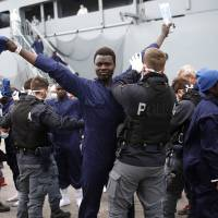 Migrants are inspected by policemen as they disembark the German naval vessel Frankfurt Am Main in the Sicilian harbor of Pozzallo, Italy, Wednesday. | REUTERS