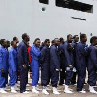 Migrants are lined up as they disembark the German naval vessel Frankfurt Am Main in the Sicilian harbor of Pozzallo, Italy, Wednesday. | REUTERS