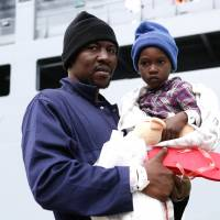 A migrant carries a child as they disembark the German naval vessel Frankfurt Am Main in the Sicilian harbor of Pozzallo on Wednesday. | REUTERS