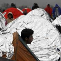 A Syrian refugee looks out of a tent at an improvised camp on the border line between Macedonia and Serbia near northern Macedonian village of Tabanovce Thursday. | AP