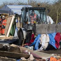 Workers demolish makeshift shelters during the dismantlement of the shanty town made by migrants called the 'Jungle' in Calais, France, Friday. | REUTERS