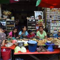 Myanmar women and children eat at a street stall in Yangon on Saturday. | AFP-JIJI