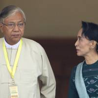 Htin Kyaw, left, newly elected president of Myanmar, walks with National League for Democracy leader Aung San Suu Kyi, right, at Myanmar's parliament in Naypyitaw, Myanmar, on March 15. | AP